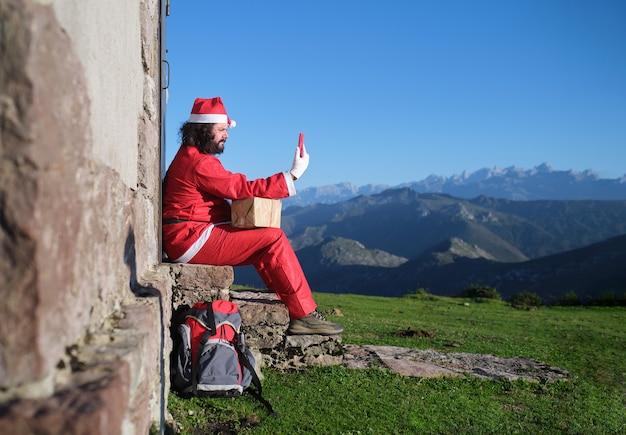 Weihnachtsmann-wanderer, der das telefon benutzt, das auf der treppe eines hauses in den bergen sitzt