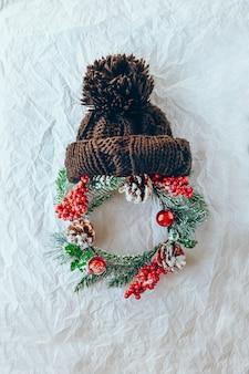 Weihnachtsmann-weihnachtskonzept aus kranz aus immergrüner fichte strickmütze