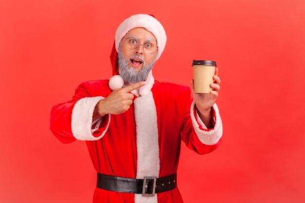 Weihnachtsmann zeigt auf kaffee, getränk mit koffein, energieschub am morgen, blick in die kamera.