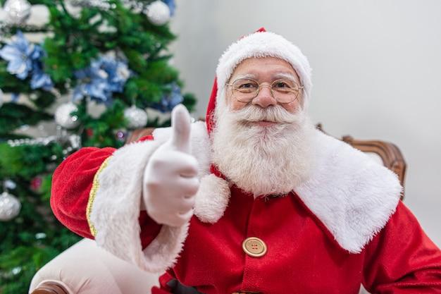 Weihnachtsmann zeigt daumen hoch. santa claus mit echtem bart und großem lächelndem aufgeben daumen.