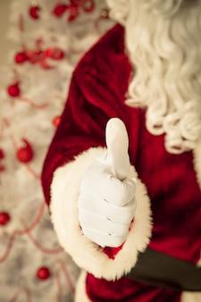 Weihnachtsmann zeigt daumen nach oben. weihnachtsferienkonzept