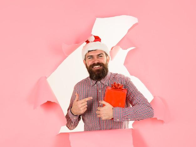 Weihnachtsmann zeigt mit finger auf geschenkbox neujahr winter weihnachtsgeschenke bärtiger mann in weihnachtsmütze