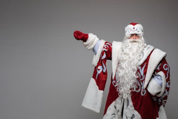 Weihnachtsmann zeigt von hand auf leeren raum