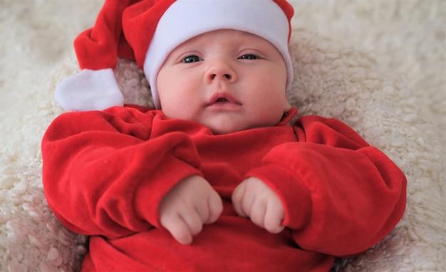Weihnachtsmannbaby, das auf weißer decke liegt. schönes kleines baby feiert weihnachten.