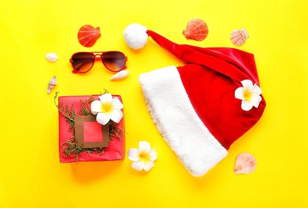 Weihnachtsmannmütze mit weihnachtsgeschenk und sonnenbrille auf farbe