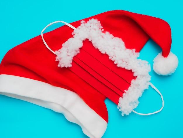 Weihnachtsmannmütze und schutzmaske auf blauem grund