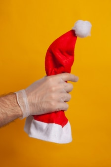 Weihnachtsmannmütze von einer hand mit einem schutzhandschuh gehalten