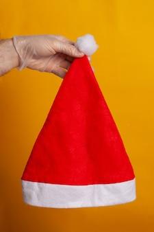 Weihnachtsmannmütze von einer hand mit schutzhandschuh gehalten