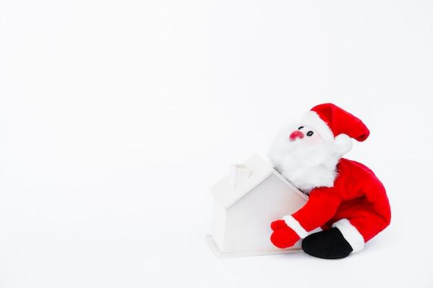 Weihnachtsmannpuppe, die ein kleines holzhaus auf lokalisiert auf weiß hält