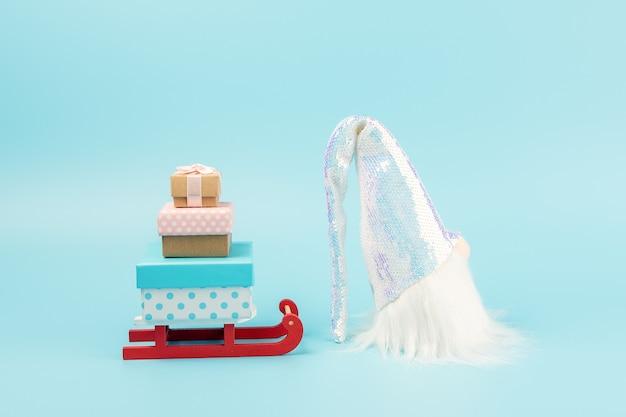 Weihnachtsmannschlitten mit geschenkboxen und weihnachtsmann auf blau