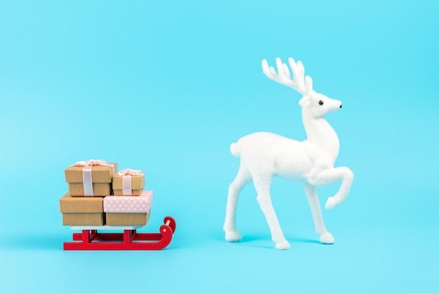 Weihnachtsmannschlitten mit geschenkboxen und weißem rentier auf blau