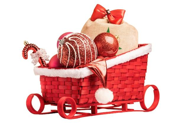 Weihnachtsmannschlitten mit roten weihnachtsballons und geschenken. an einer weißen wand isolieren.