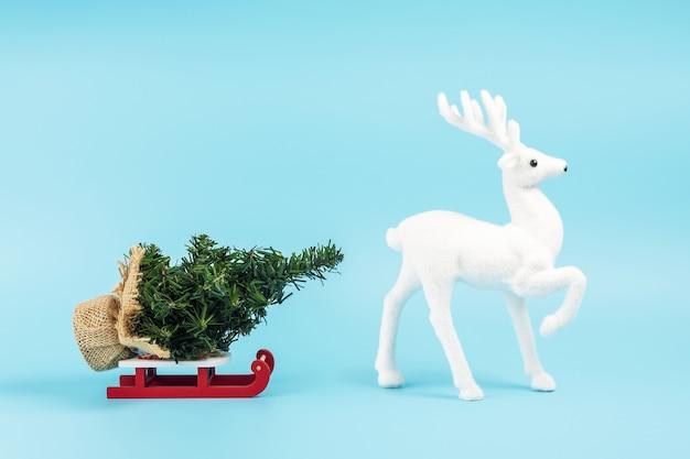 Weihnachtsmannschlitten mit weihnachtsbaum und weißem rentier auf blau