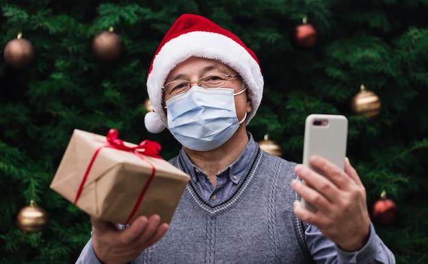 Weihnachtsmaske glückwünsche. porträtfrau, die weihnachtsmütze und weißen pullover in der medizinischen maske trägt und geschenkgeschenkbox mit rotem band, weihnachtsbaum bokeh auf hintergrund gibt