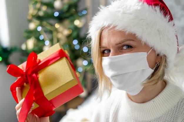Weihnachtsmaske glückwünsche. porträtfrau in der medizinischen maske und im weihnachtsmann mit geschenkgeschenkbox