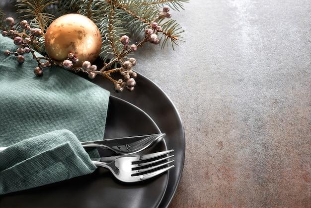 Weihnachtsmenü mit verzierten schwarzen tellern und tischbesteck