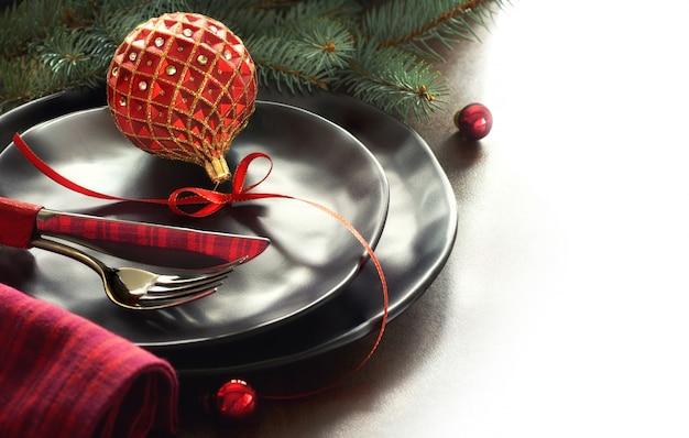 Weihnachtsmenükonzept mit verzierten schwarzen tellern und besteck