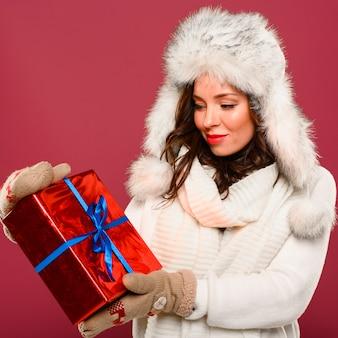 Weihnachtsmode-modell, das geschenk betrachtet