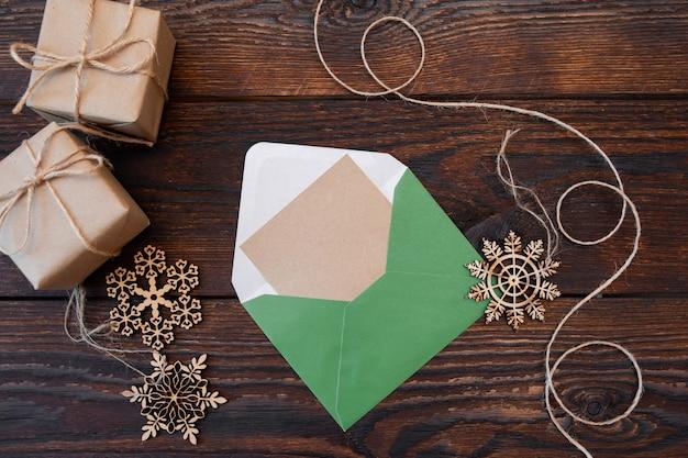 Weihnachtsmodell feiertagsbrief leeres papier in grünem umschlag mit hölzernen schneeflocken und geschenkboxen.