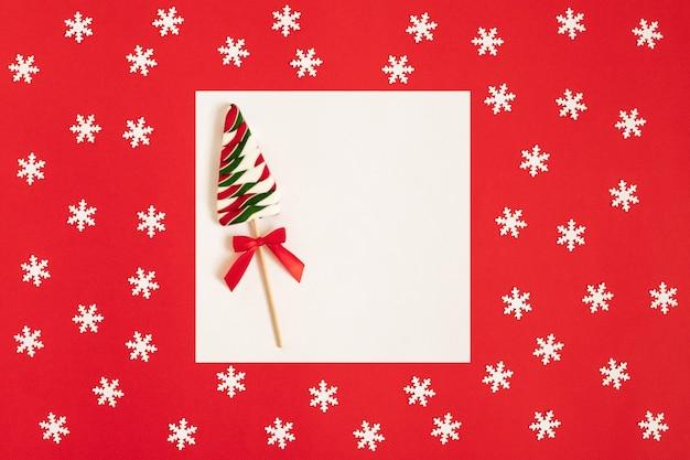 Weihnachtsmodell mit lutscher in form eines weihnachtsbaumes auf rotem grund.