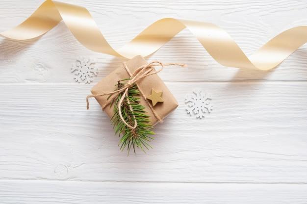 Weihnachtsmodellkraftpapier-geschenkboxhintergrund mit beige band auf weißem holz