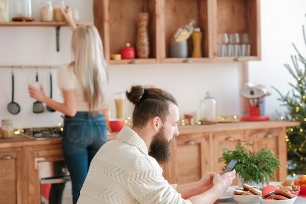Weihnachtsmorgen. dame, die frühstück in der modernen küche macht. kerl, der am tisch sitzt, mit smartphone.