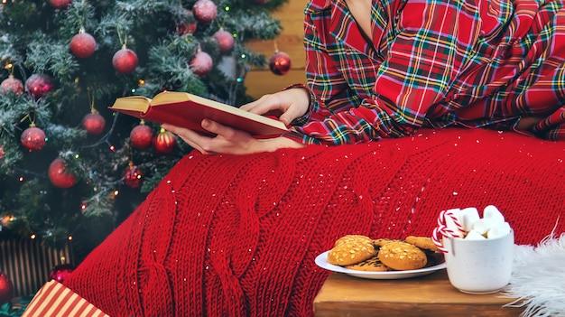 Weihnachtsmorgen, frau im schlafanzug mit einem buch. tiefenschärfe.