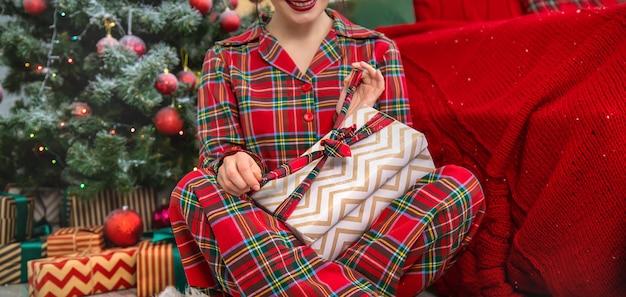 Weihnachtsmorgen, frau mit geschenken in ihren händen. tiefenschärfe.