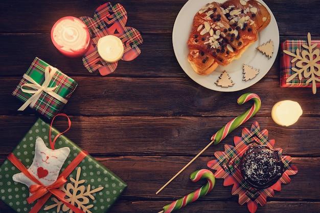 Weihnachtsmorgen tisch mit croissant, süßigkeiten und geschenken Premium Fotos