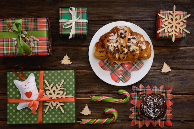 Weihnachtsmorgen tisch mit croissant, süßigkeiten und geschenken
