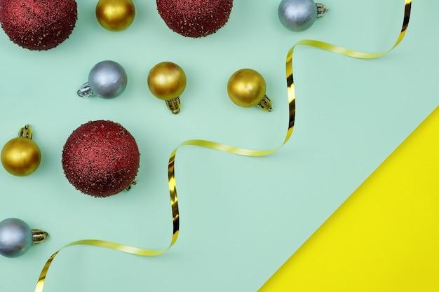 Weihnachtsmotivkugel und goldband auf heller hintergrundoberansicht.