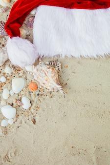 Weihnachtsmütze am strand. weihnachtsmütze auf dem sand in der nähe von muscheln.