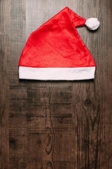 Weihnachtsmütze auf hölzernen hintergrund. flat lay für weihnachten und happy new year banner.