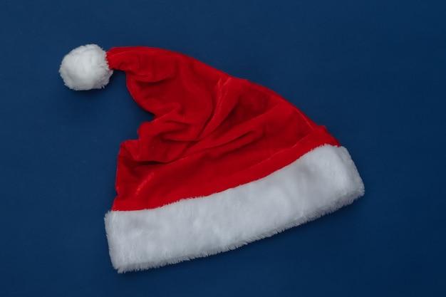 Weihnachtsmütze auf klassischem blauem hintergrund. farbe 2020. weihnachtsthema. ansicht von oben