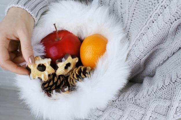 Weihnachtsmütze gefüllt mit weihnachtsgeschenken in frauenhänden