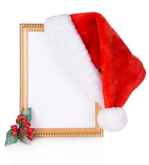 Weihnachtsmütze hing am alten rahmen isoliert auf weiß