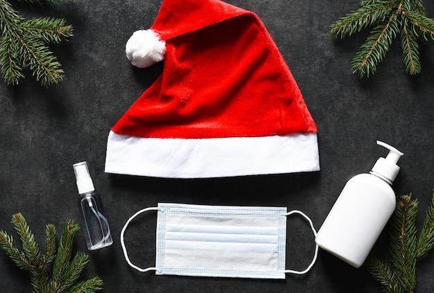 Weihnachtsmütze, medizinische maske und antiseptikum auf einem schwarzen betonhintergrund.