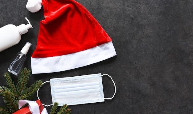 Weihnachtsmütze, medizinische maske und geschenk auf einem schwarzen betonhintergrund.