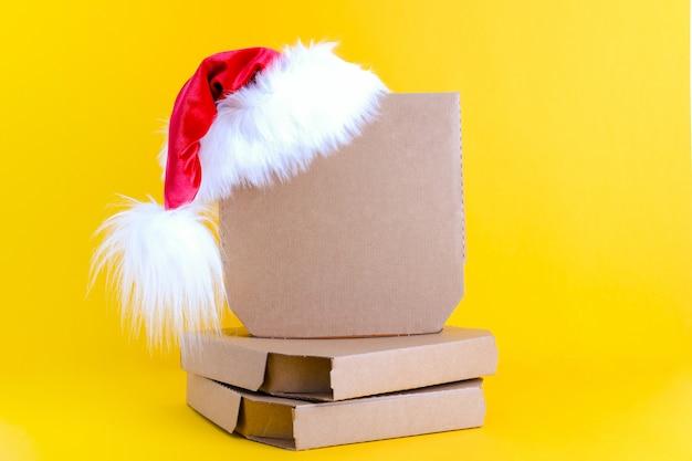 Weihnachtsmütze mit drei pizzakartons