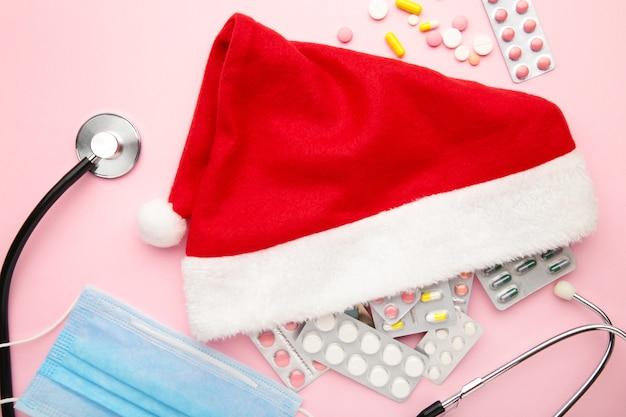 Weihnachtsmütze mit medizin und gesichtsmaske