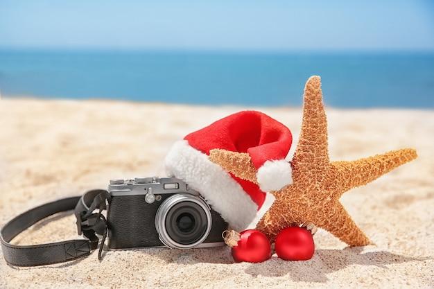 Weihnachtsmütze mit seestern, kamera und dekorationen am strand. weihnachtsferienkonzept