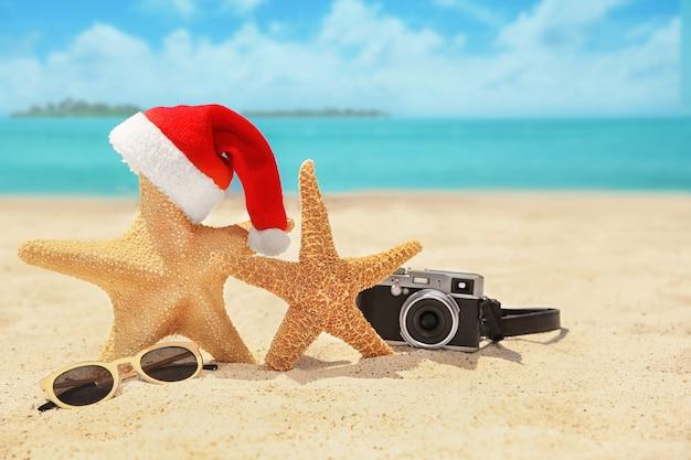 Weihnachtsmütze mit seesternen, kamera und sonnenbrille am strand. weihnachtsferienkonzept