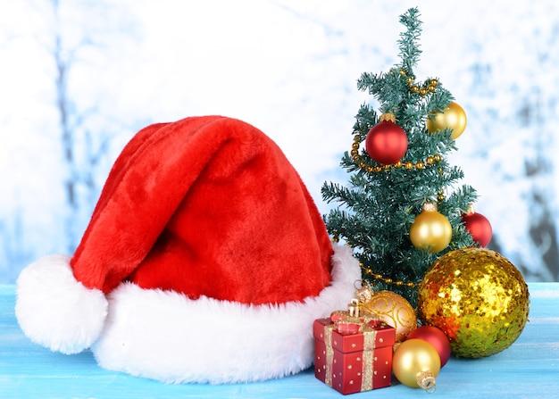 Weihnachtsmütze mit weihnachtsschmuck auf dem tisch auf hellem hintergrund