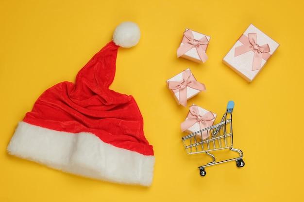 Weihnachtsmütze, schachteln mit geschenken und einkaufswagen auf gelbem hintergrund. weihnachtswohnung lag. draufsicht