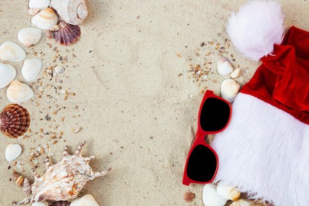 Weihnachtsmütze und brillen auf dem sand in der nähe von muscheln. urlaub. neujahrsurlaub.