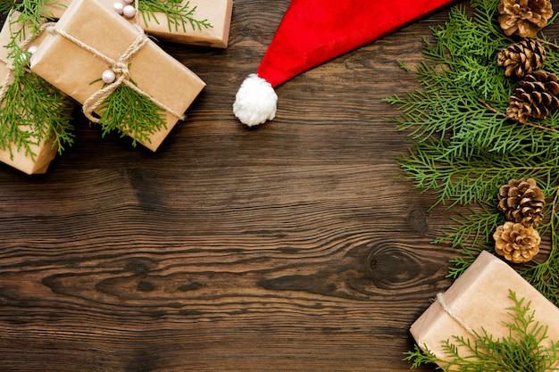 Weihnachtsmütze und geschenkboxen auf dunklem holzbrett mit kopierraum