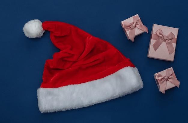 Weihnachtsmütze und geschenkboxen auf klassischem blauem hintergrund. farbe 2020. weihnachtsthema. ansicht von oben