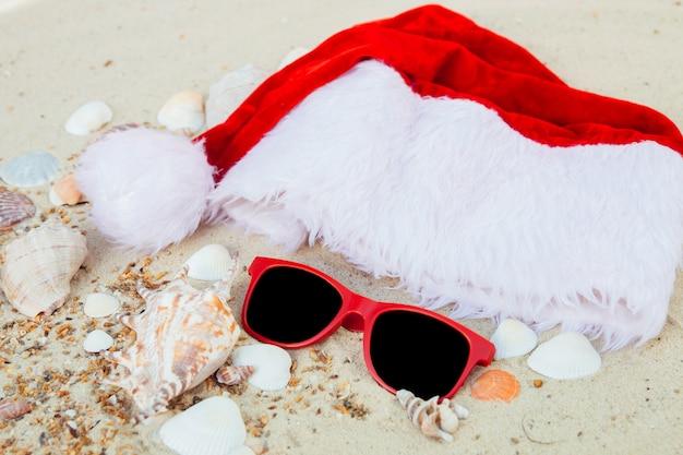 Weihnachtsmütze und rote sonnenbrille am strand. weihnachtsmütze und brillen auf dem sand in der nähe von muscheln. urlaub. neujahrsurlaub.
