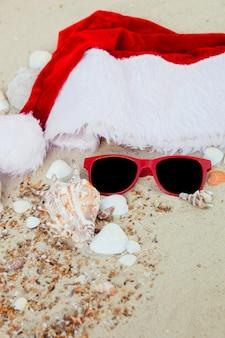 Weihnachtsmütze und rote sonnenbrille am strand