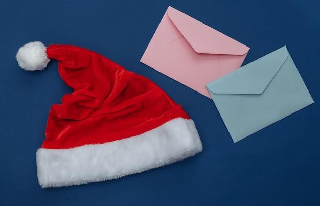 Weihnachtsmütze und umschläge auf klassischem blauem hintergrund. farbe 2020. weihnachtsthema. ansicht von oben
